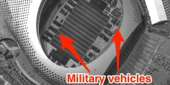 Satellite photos show more than 100 Chinese military vehicles massed at a soccer stadium near the Hong Kong border